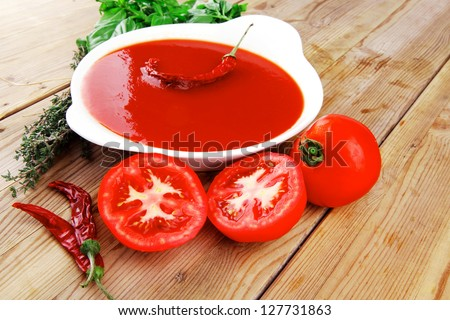 hot fresh diet tomato soup with basil thyme and raw tomatoes in white round bowl over red mat on wood table ready to eat