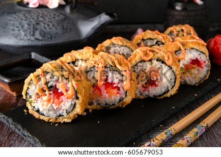 Hot fried Sushi Roll with salmon, eel, calf caviar and cheese. Sushi menu. Japanese food. Hot fried Sushi Roll