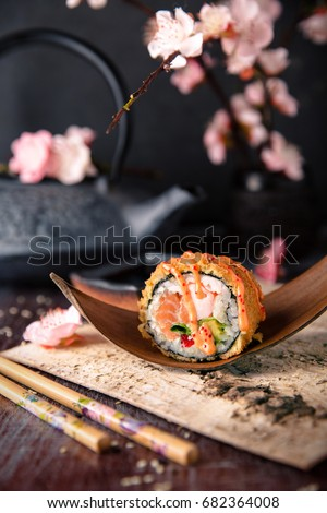 Hot fried Sushi Roll with salmon, shrimp, onion, avocado and cheese. Sushi menu. Japanese food. Royal sushi roll