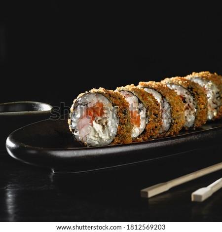 Hot fried sushi roll with salmon. Sushi menu. Japanese food. Hot fried sushi roll on black background