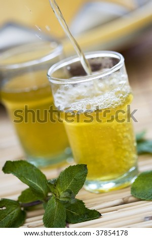 Hot green mint tea being poured into a glass. Moroccan style. - stock photo