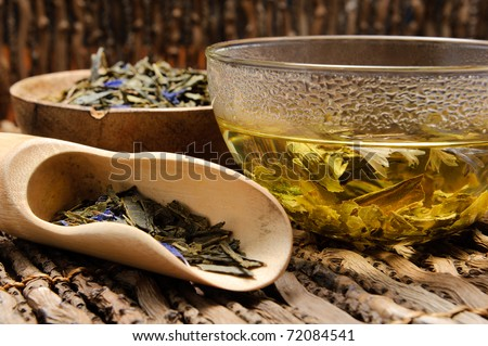 Hot green tea in a glass cup with a tea leafs on wooden shovel. Shallow Depth of Field (Focus on tea)