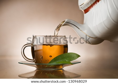 Hot green tea pouring in to cup close up