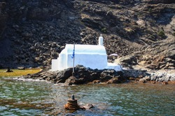 Hot, healing springs at the foot of the Greek island of Palea Kameni, next to a white chapel - the symbol of the island