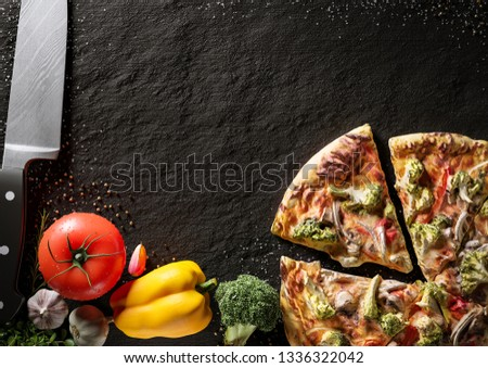 Hot Italian pizza on a black stone plate. Around are fresh tomatoes in drops of water, sweet and spicy peppers, greens, spices, salt and black pepper. Ideal for the restaurant menu or for intro video #1336322042