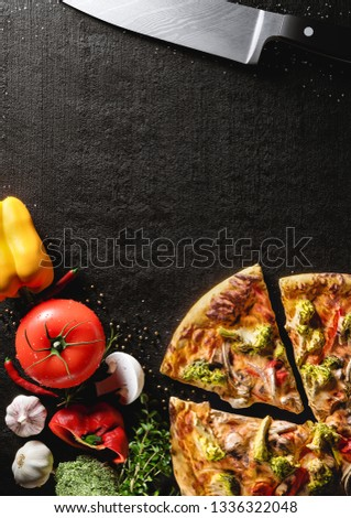 Hot Italian pizza on a black stone plate. Around are fresh tomatoes in drops of water, sweet and spicy peppers, greens, spices, salt and black pepper. Ideal for the restaurant menu or for intro video #1336322048