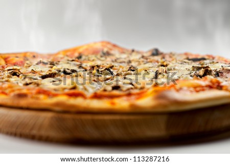 Hot Italian pizza with cheese, mushrooms and ham on a wooden support on a white background