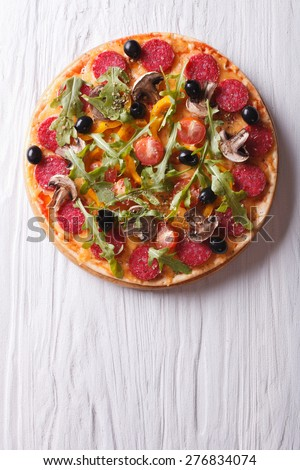Hot Italian pizza with rocket salad and salami, vertical view from above