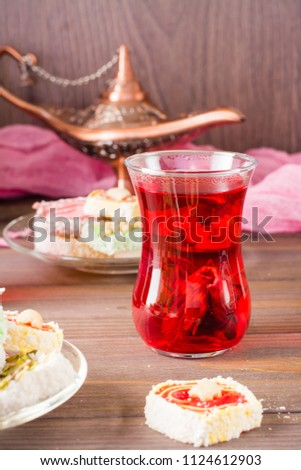 Hot karkade in cups and  Turkish Delight on a plate  on a wooden table Stockfoto ©