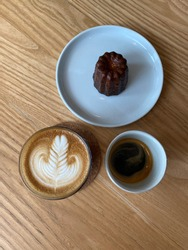 Hot latte art coffee served with the Canelé (Canele) de Bordeaux, French bakery pastry confection -rich custardy interior enclosed by a thin caramelized shell
