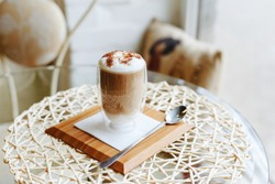 Hot latte or Cappuccino coffee on a table in a cafe near the window with copy space. Latte coffee with milk and chocolate on top in a double walled glass on a serving board with a spoon.
