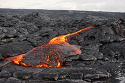 Hot magma of an active lava flow emerges from a fissure, the heat of the glowing lava makes the air flicker, the lava cools down slowly and solidifies - Hawaii, Big Island, Kilauea volcano, Kalapana