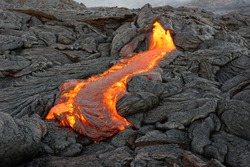 Hot magma of an active lava flow emerges from a rock fissure, the glowing lava makes the air flicker with heat, the lava cools down slowly and solidifies in bizarre patterns - Hawaii, Big Island