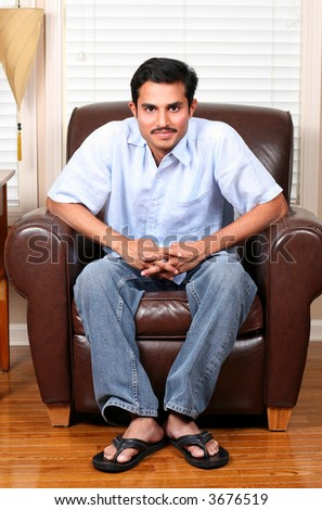 hot man with mustache seated at home