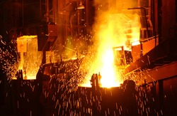 Hot metal pours from a blast furnace with sparks