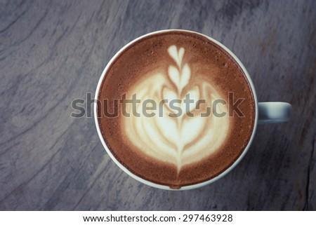 hot milk art coffee on wooden table , Vintage latte art coffee
