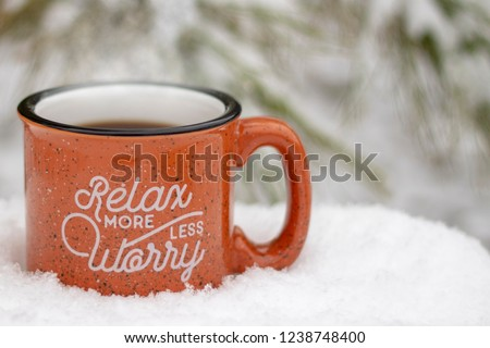 Hot mug steam rising relax more worry less message on front surrounded by snowy scene & icy pine branches in winter background, holiday stress keep calm relax more worry less concept, text copy space