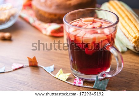 Hot mulled wine from Brazil with apple pieces, tipical in Festa Junina Festival. Traditional food of Brazil, June Partys sweet. Rustic Wood Background with peanuts and brazilian candys