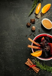 Hot mulled wine with orange slices, anise and cinnamon sticks on black chalkboard from above. Christmas or winter warming drink with recipe ingredients around. Layout with free text space.
