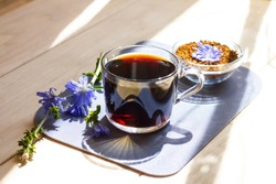 Hot natural chicory caffeine free drink in a transparent cup on a wooden table outdoors. Healthy alternative replacement for coffee, caffeine. Blue chicory flower. Beautiful summer morning at nature