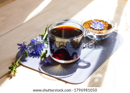 Hot natural chicory caffeine free drink in a transparent cup on a wooden table outdoors. Healthy alternative replacement for coffee, caffeine. Blue chicory flower. Beautiful summer morning at nature Foto stock ©