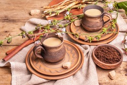 Hot natural chicory caffeine free drink in ceramic cups on a wooden table. Healthy alternative replacement for coffee, caffeine. Blue chicory flowers, fresh roots, close up
