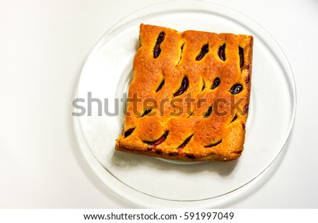 hot natural fresh sweet homemade cake with plumps and texture-baked dough cut into square against clear glass plate. Peace of home holiday cake as best addition to a cup of coffee or tea