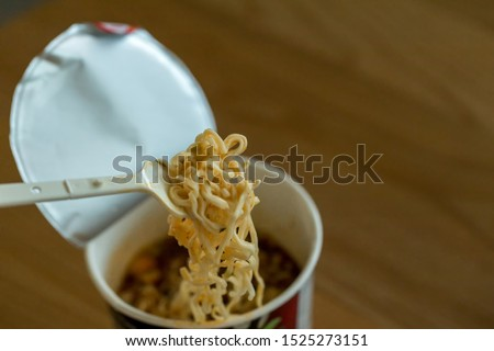 Hot noodle Cup. Noodle cup Ready made. Eating Instant Noodles with a Plastic Fork. Junk food Instant noodles are eating the popular food. #1525273151