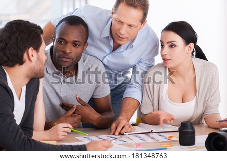 Hot office discussion. Group of cheerful business people sitting together at the table and discussing something