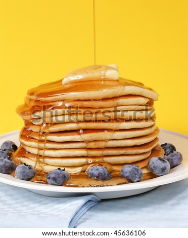 Hot pancake staked with blueberry fruit on a yellow background. Melted butter on the top with maple syrup falling on it.