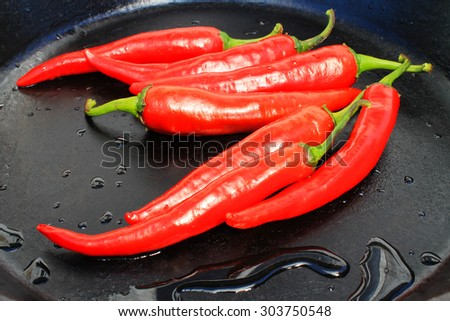 hot pepper on a black frying pan with water drops