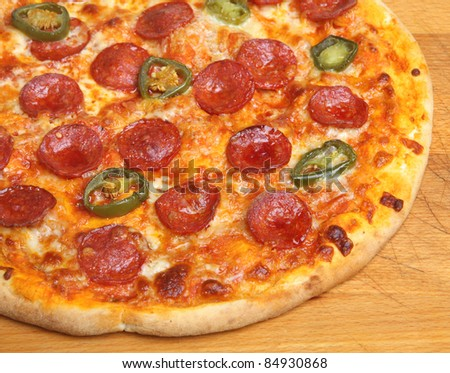 Hot pepperoni pizza with green chillies.