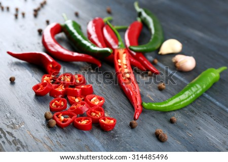 Hot peppers with spices on wooden table close up