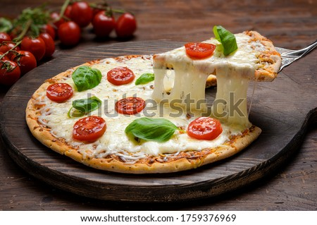 Hot pizza  and slice with melting cheese pull.