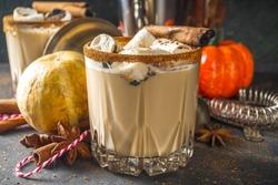 Hot pumpkin spice cocktail, pumpkin white russian cocktail, with marshmallow and pumpkin spices, dark background copy space