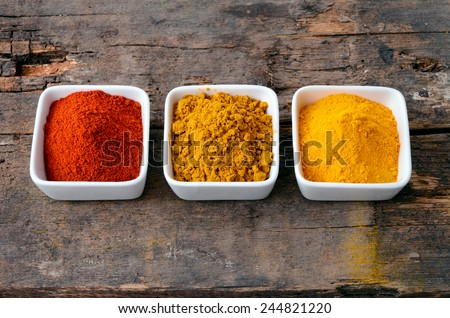Hot red chili powder, curry and turmeric powder on wooden background