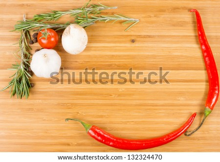 Hot red chilli peppers, garlic, tomato, mushroom and rosemary arranged as a border on a wooden background with central copyspace