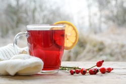 Hot red rose hip tea with a lemon slice in a glass mug on a rustic wooden table against a frosty winter landscape, copy space, selected focus, narrow depth of field