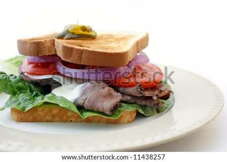 Hot roast beef sandwich with melted cheese, lettuce, tomato, and red onion on a plate with white background