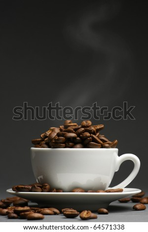 Hot roasted coffee beans in white cup with saucer on dark gray background.