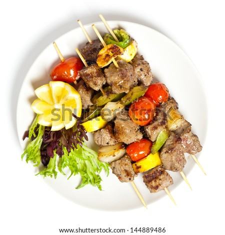 Hot roasted meat with onion, tomato and pepper on the skewer