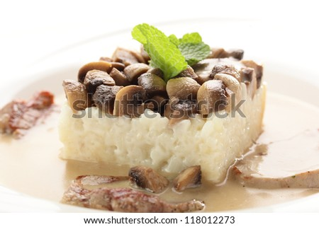 hot roasted meat with rice and mushrooms on white background