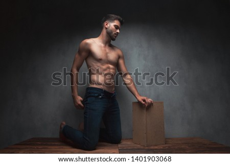 Hot shirtless guy pulling his jeans and kneeing while leaning on a box and looking to the side on gray studio background