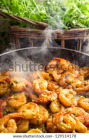 Hot shrimp fried in a pan with herbs