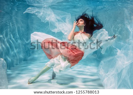 Photo of Hot Slim Brunette Woman Posing Under water in beautiful clothes alone in the deep