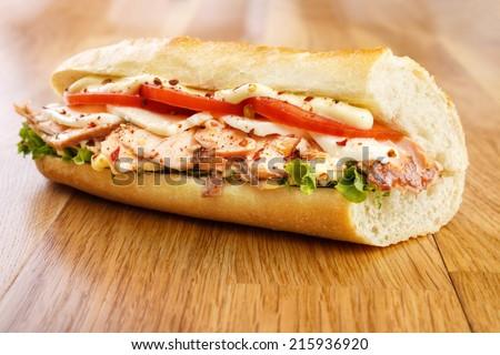 Hot smoked salmon sandwich with tomato , mozzarella cheese , lettuce and mayonnaise