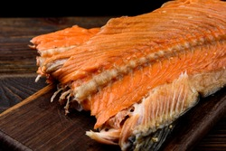Hot smoked salmon trim and leftovers with bones and fins on dark wooden background.