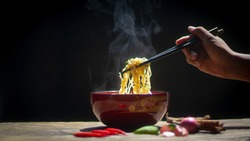 Hot soup noodles with smoke on the table in a bowl and hand chopsticks with mama-concept Asian dishes