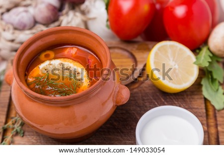 hot soup saltwort with garnish in brown ceramic pot