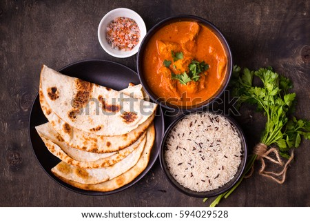 Hot spicy chicken tikka masala in bowl. Chicken curry with rice, indian naan butter bread, spices, herbs. Traditional Indian/British dish, popular indian curry in UK. Top view. Indian food. Close-up